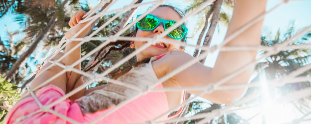 Young girl wearing sunglasses and smiling on a hammock.