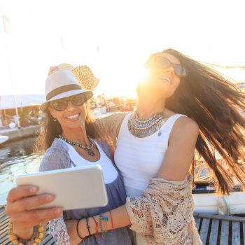 Two women taking a selfie near a marina.